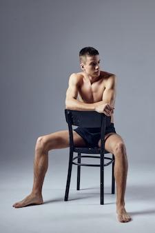 Śliczne czarne szorty facet siedzący na krześle wyglądają na boczne studio