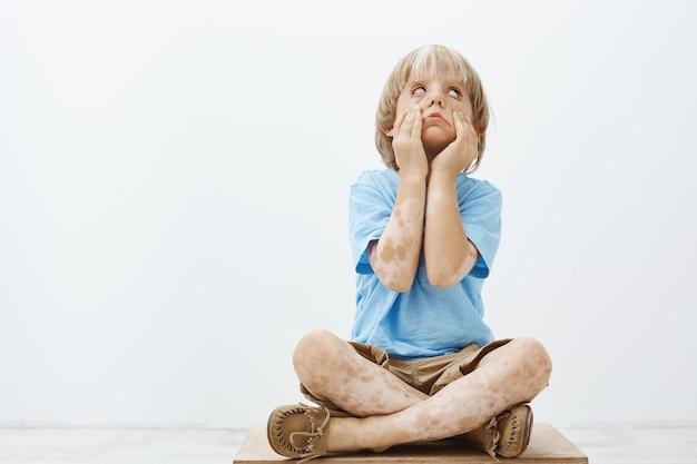 Śliczne, dobrze wyglądające dziecko z dwukolorową skórą, siedzące ze skrzyżowanymi stopami, przewracające powiekami i wyciągające oczy rękami, znudzone podczas kary