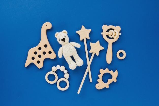 Śliczne drewniane zabawki dla dzieci. dzianinowy miś, tęcza, zabawka dinozaur, koraliki i gwiazdki.