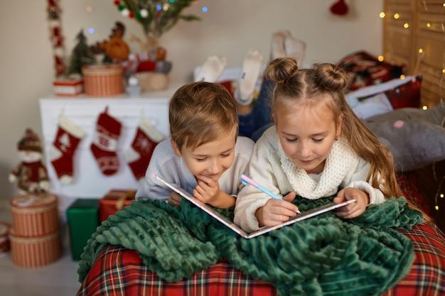 Śliczne dwoje szczęśliwych dzieci pisze list do świętego mikołaja
