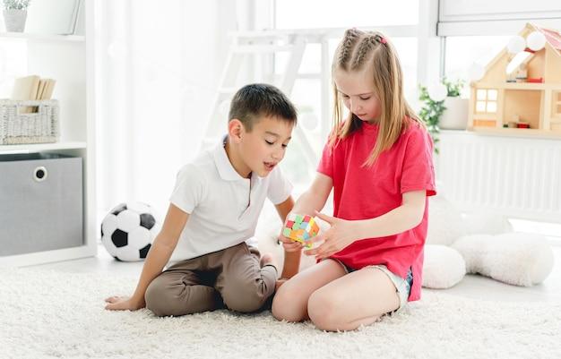 Śliczne dzieci bawiące się kostką rubika