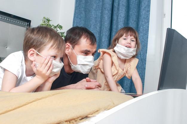 Śliczne dzieci chłopiec, dziewczynka i ich ojciec w masce medycznej siedzą w domu w kwarantannie.