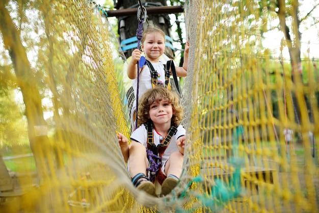 Śliczne dzieci - chłopiec i dziewczynka w parku rozrywki zajmują się wspinaczką skałkową lub omijają przeszkody na drodze linowej.