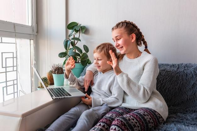 Śliczne dzieci o rozmowie wideo z dziadkami na laptopie zostań w domu, koncepcja komunikacji na odległość