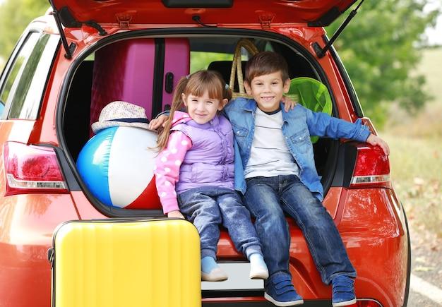 Śliczne dzieci w pobliżu nowoczesnego samochodu przygotowanego do podróży