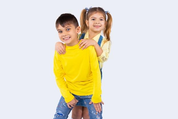 Śliczne dzieci w wieku przedszkolnym uśmiechnięte i pozujące w ubranie na białym tle z boczną przestrzenią.