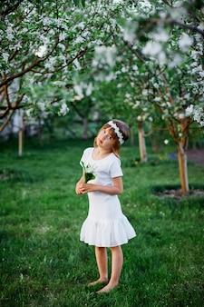 Śliczne dziecko dziewczynka 5-6 lat trzyma kwiat stojący w kwitnącym wiosennym ogrodzie, ubrana w białą sukienkę i kwiatowy wianek na zewnątrz, zbliża się sezon wiosna.