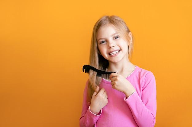 Śliczne dziecko, dziewczynka w wieku 6-8 lat czesze grzebieniem średniej długości miękkie włosy blond i uśmiecha się na pomarańczowej ścianie