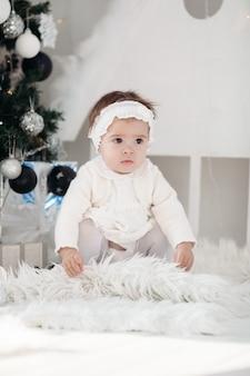 Śliczne dziecko kobiece na sobie bardzo piękną białą sukienkę i siedzi na dywanie z choinką w domu. koncepcja wesołych świąt