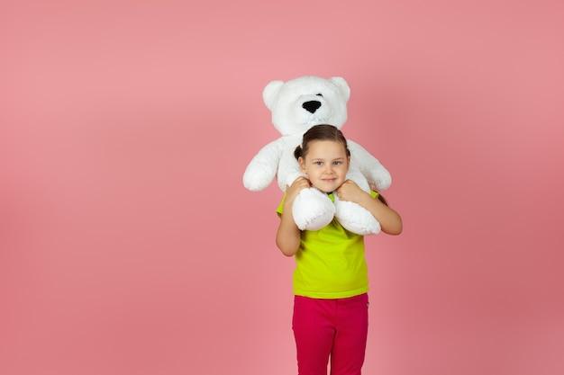Śliczne dziecko z warkoczykami w jasnozielonej koszulce założyło na ramiona białego misia