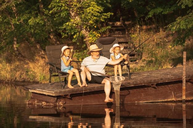 Śliczne dziewczynki i ich dziadek łowią ryby nad jeziorem lub rzeką. odpoczynek na molo w pobliżu wody i lasu w porze zachodu słońca w letni dzień. pojęcie rodziny, rekreacji, dzieciństwa, przyrody.