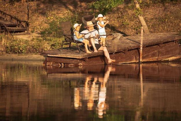 Śliczne dziewczynki i ich dziadek łowią ryby nad jeziorem lub rzeką