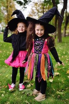 Śliczne dziewczynki w kostiumach na halloween i duże czarne czapki wiedźmy podczas obchodów halloween w parku