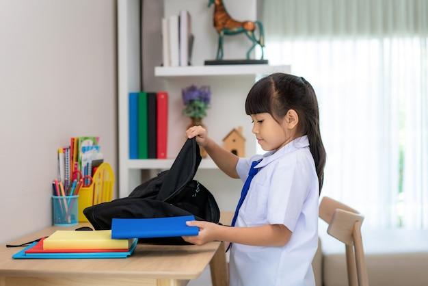 Śliczne dziewczynki ze szkoły podstawowej pakujące tornistry, przygotowujące się do pierwszego dnia w szkole.