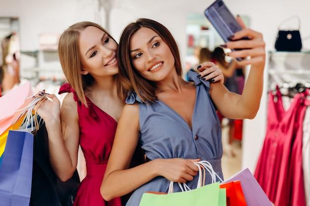 Śliczne dziewczyny robią zakupy w butiku i robią selfie ze smartfonem