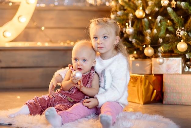 Śliczne dziewczyny świętują boże narodzenie przy drzewie nowego roku