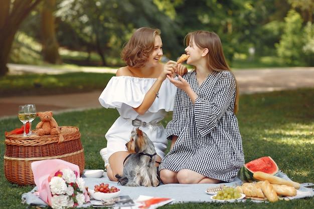 Śliczne dziewczyny w parku bawiące się z małym psem