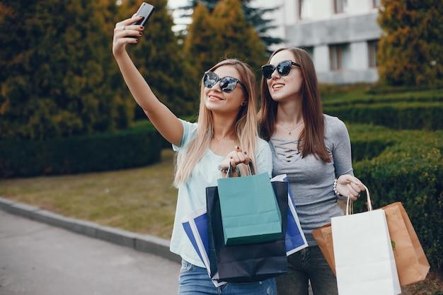 Śliczne dziewczyny z torba na zakupy w mieście