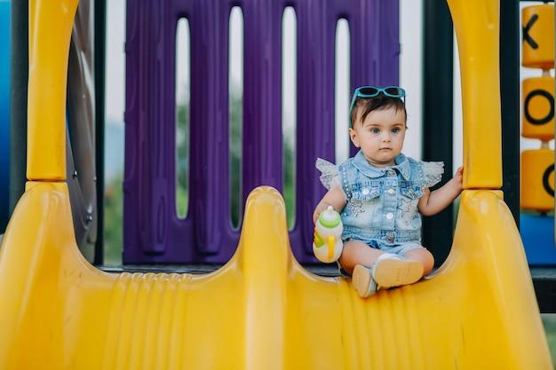 Śliczne dziewięciomiesięczne dziecko siedzi na slajdzie na placu zabaw i trzymając zabawkę smoczek