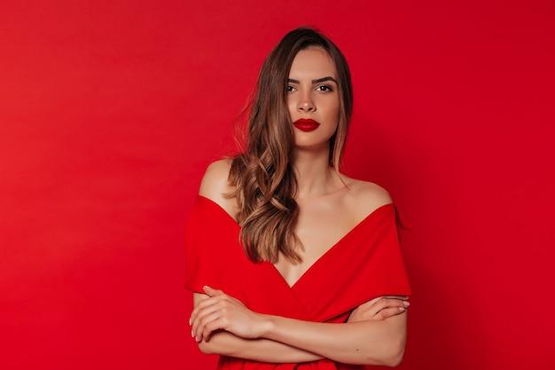 Śliczne falowane włosy kobieta z czerwoną jasną szminką w stylowej czerwonej sukience, uśmiechając się i pozując na na białym tle