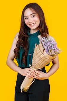 Śliczne i całkiem kręcone włosy azjatycka brunetka trzyma bukiet kwiatów z wesołą i szczęśliwą, studio strzał na białym tle na jasnożółtym tle.