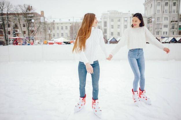 Śliczne i piękne dziewczyny w białym swetrze w zimowym mieście
