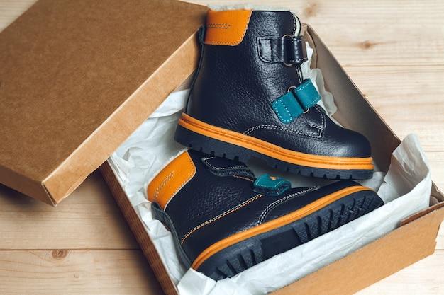 Śliczne jesienne buty dziecięce w kartonowym pudełku na drewnianej podłodze. widok z góry