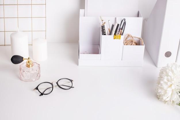 Śliczne kobiece rzeczy na białym stole z okularami i kwiatem, biuro, widok z boku
