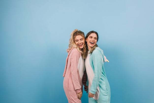 Śliczne kobiety pozują w kigurumi na niebieskiej ścianie