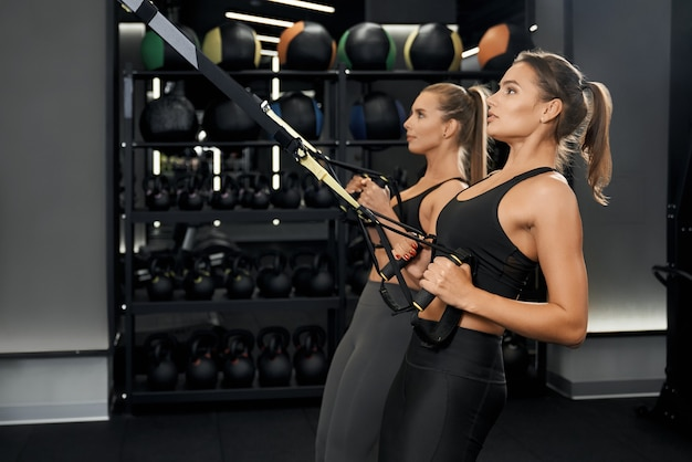 Śliczne kobiety robią trening z systemem trx w siłowni