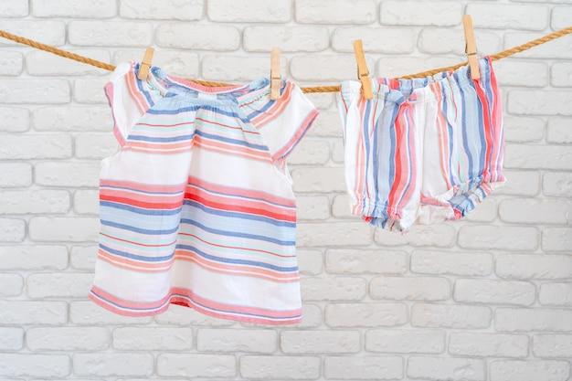 Śliczne kolorowe ubrania malucha wiszą na linie