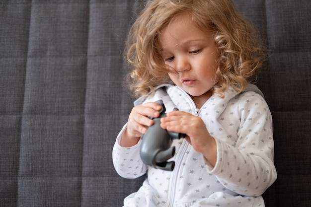 Śliczne kręcone maluch dziewczyna bawi się z zabawkami hipopotam w zoo siedzi na kanapie. zabawki dla małych dzieci. wczesny rozwój