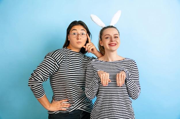 Śliczne króliczki. młode emocjonalne kobiety na białym tle na gradientowym niebieskim tle studio. pojęcie ludzkich emocji, wyraz twarzy, przyjaźń, reklama. piękne kaukaski modelki w ubranie.