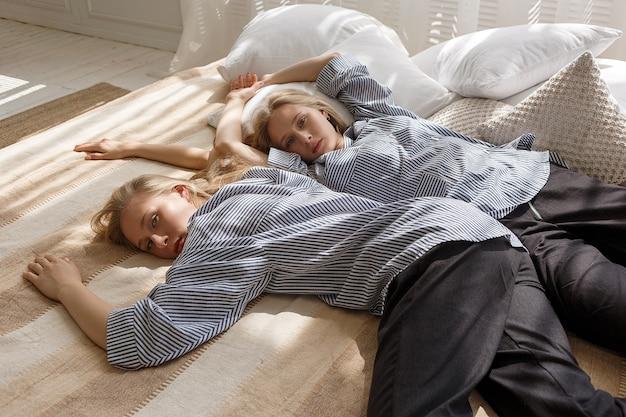 Śliczne ładne bliźniaczki z długimi blond włosami w pasiaste koszule i czarne spodnie leżą w łóżku