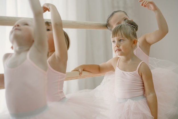 Śliczne małe balerinki w różowym stroju baletowym. w pokoju tańczą dzieci w pointach. dziecko w klasie tańca.