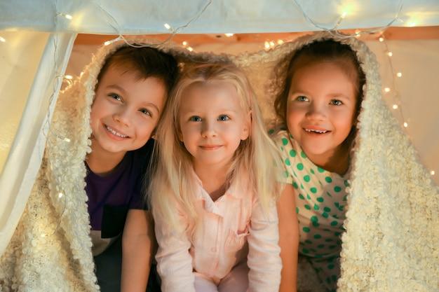 Śliczne małe dzieci bawiące się w ruderze w domu