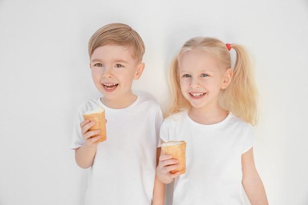 Śliczne małe dzieci jedzą lody na białym tle