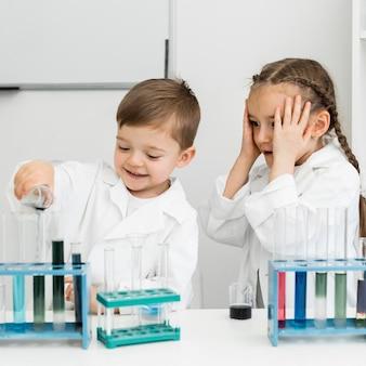 Śliczne małe dzieci naukowcy z probówkami robią doświadczenia