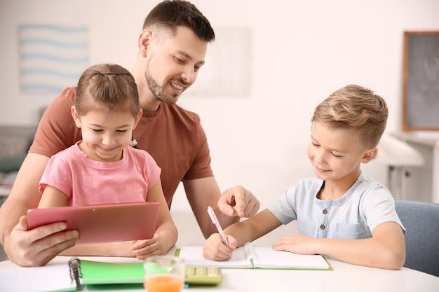 Śliczne małe dzieci odrabiają pracę domową z ojcem