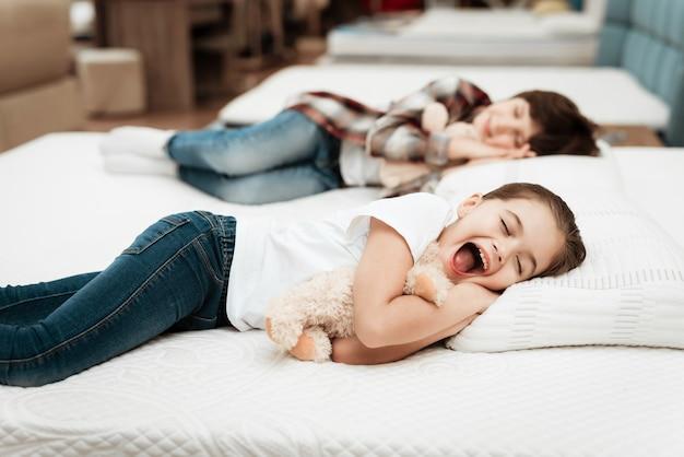 Śliczne małe dzieci śpiące na materacu w sklepie