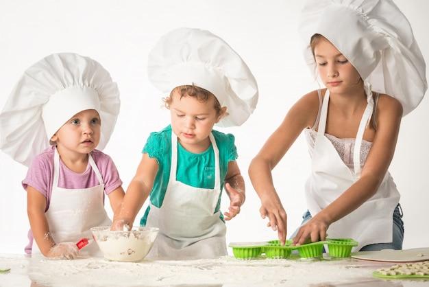 Śliczne małe dzieci w fartuchu robi ciastkom