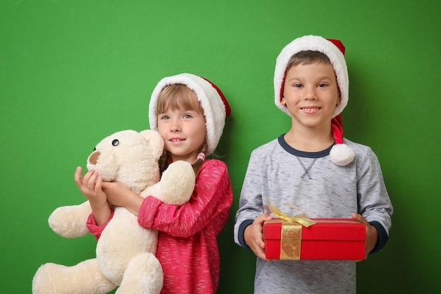 Śliczne małe dzieci z prezentami świątecznymi na kolorowym tle