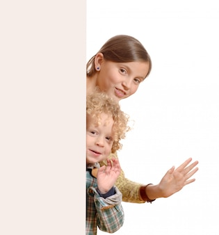 Śliczne małe dzieci za białą deską