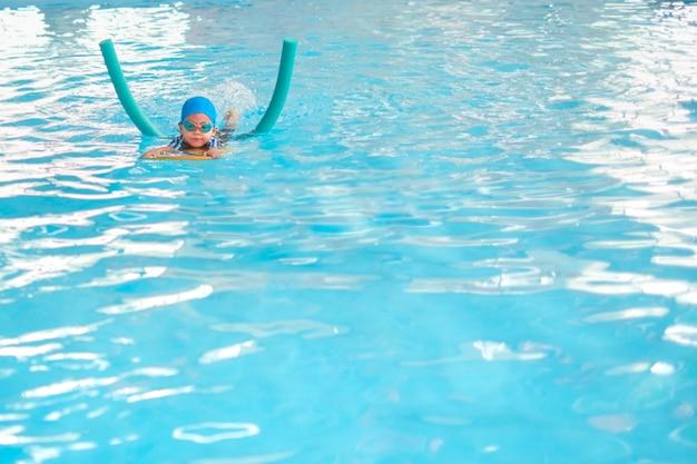Śliczne małe dziecko azjatyckie dziecko chłopiec kopanie stóp w kostiumie pływackim nosić okulary pływackie używać basen makaron i kickboard nauczyć się pływać w krytym basenie