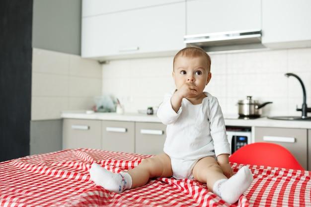 Śliczne małe dziecko siedzi na stole w kuchni
