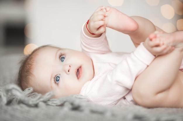 Śliczne małe dziecko w domu w sypialni. niemowlę w pomieszczeniu. portret dziecka w 6. miesiącu życia. urocza śliczna dziewczynka.