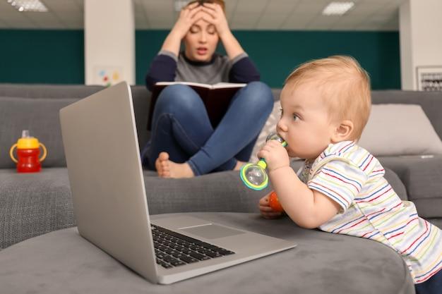 Śliczne małe dziecko z laptopem ze zmęczoną matką w domu