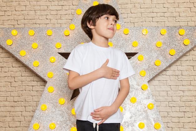 Śliczne małe dziecko z przodu w białych ciemnych dżinsach z podkoszulkiem na gwiazdowym żółtym stojaku i jasnym tle