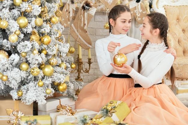 Śliczne małe dziewczynki dekorują choinkę i pozują w domu