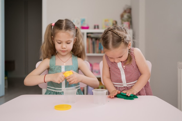 Śliczne małe dziewczynki formuje z plasteliny na różowym stole